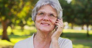 资深妇女谈话在智能手机在公园 免版税图库摄影