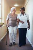 资深妇女走的被帮助由女性护士 免版税库存照片