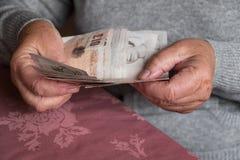 资深妇女递拿着金钱,英镑 免版税库存照片