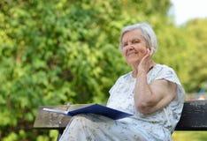 资深妇女阅读书在公园 免版税图库摄影