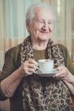 资深妇女饮用的咖啡和微笑 免版税库存图片
