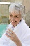 资深妇女饮用的石灰水户外 库存图片