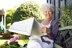资深妇女读书报纸在后院庭院里 图库摄影
