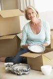 资深妇女移动的家和包装盒 库存图片