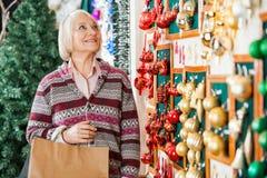 资深妇女购物圣诞节装饰品 库存照片