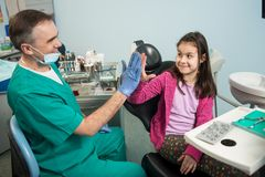 资深小儿科牙医和可爱的孩子在对待牙在牙齿诊所办公室,微笑和给以后高五 库存照片