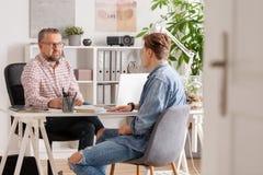 资深帐户经理和年轻人在面试中在小公司 免版税图库摄影