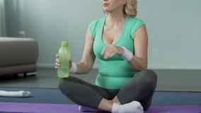 资深年龄的女性坐健身席子,饮用水,体育活动 股票录像