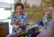 资深愉快和甜亚洲日语生活方式画象退休了,在家烹调厨房的妇女洗盘子 免版税图库摄影