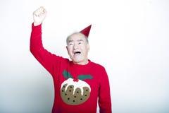资深成人人佩带的圣诞节套头衫在天空中的举他的胳膊 库存图片