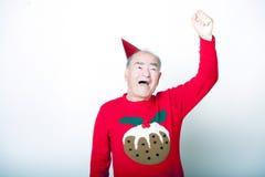 资深成人人佩带的圣诞节套头衫在天空中的举他的胳膊 库存照片