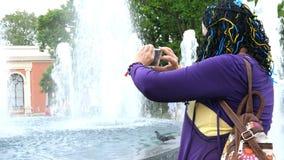 资深成人妇女旅客,采取被拍摄的照片或录影关于美丽的喷泉有她的智能手机的 股票视频