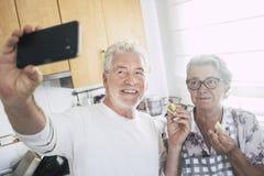 资深成人白种人愉快的夫妇在家在烹调和运作与喜悦和幸福一起的厨房里 ??selfie? 免版税图库摄影