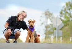 资深成熟人&爱犬在户外步行 免版税库存图片
