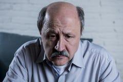 资深成熟老人画象他的60s在家长沙发单独感觉哀伤和担心的遭受的痛苦和消沉的 免版税图库摄影