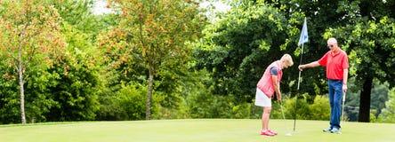 资深打高尔夫球的妇女和人投入在绿色 图库摄影