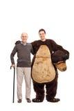 资深摆在与熊服装的一个人 免版税库存图片