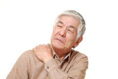 资深日本人遭受脖子疼痛 免版税库存照片