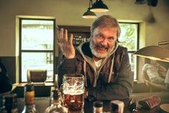 资深有胡子的男性饮用的啤酒在客栈 库存照片