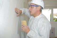 资深有铺沙的海绵的建造者铺沙的墙壁 免版税图库摄影