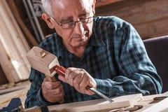 资深木匠与工具一起使用 库存图片