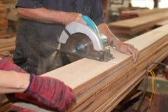 资深木匠在木匠业车间切开一块木头与电圆锯的 免版税库存图片
