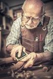资深木匠铺沙的椅子 免版税库存照片
