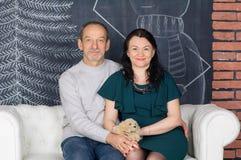 资深灰发的人坐拥抱他的深绿礼服的白色沙发中年妻子 愉快的加上年龄 免版税库存照片