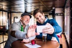资深父亲和他的年轻儿子有智能手机的在客栈 免版税库存照片