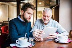 资深父亲和年轻儿子有片剂的在咖啡馆 库存照片