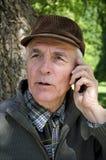 资深电话在树下 免版税库存图片