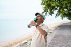 资深男性亚洲人饮用水瓶 免版税图库摄影
