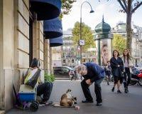 资深男性停下来与在巴黎街道上的两只猫聊天 库存图片
