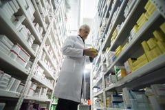 资深男性在药房的化学家支持的架子 库存图片