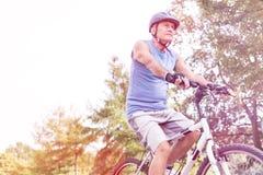 资深男性运动员骑马自行车在公园 免版税库存图片