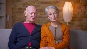 资深白种人配偶在客厅观看电视新闻是殷勤的在沙发 影视素材