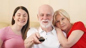 资深看电视的夫妇和青少年的女儿 背景河槽控制现有量远程开关白色 一起享受时间的愉快的家庭 股票录像