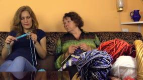 资深祖母和年轻孙女谈话并且编织 股票录像