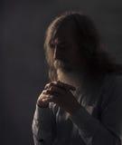 资深祷告,祈祷用在黑暗的被折叠的手的老人 免版税图库摄影