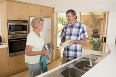 资深美好的中年夫妇大约70岁洗盘子的微笑的愉快的在家厨房一起看起来甜 免版税库存照片