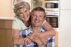 资深美好的中年夫妇大约70岁看起来微笑的愉快的一起在家的厨房甜在终身的丈夫 库存照片