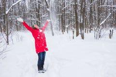 资深老妇人投掷在木头的雪在红色外套 免版税图库摄影
