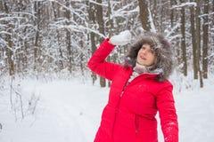 资深老妇人投掷在木头的雪球在红色外套 免版税库存照片
