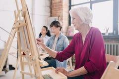 资深艺术家绘画在艺术演播室 库存图片