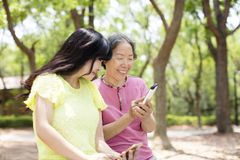资深观看巧妙的电话的母亲和daughter免版税库存图片