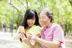 资深观看巧妙的电话的母亲和daughter库存照片