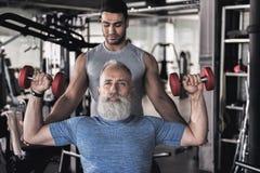 资深运动员在运动中心的做锻炼与他的辅导员 库存照片