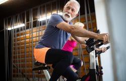 资深适合的做在健身房的男人和妇女锻炼停留健康 免版税库存图片