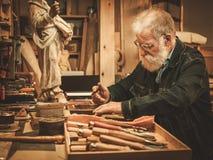 资深重建者与古色古香的装饰元素一起使用在他的车间 免版税库存图片
