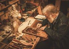 资深重建者与古色古香的装饰元素一起使用在他的车间 免版税库存照片